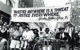 "People march in a parade led by people rolling in wheelchairs.  The hold a large banner that says: ""An injustice anywhere is an injustic everywhere - Martin Luther King, Jr."""