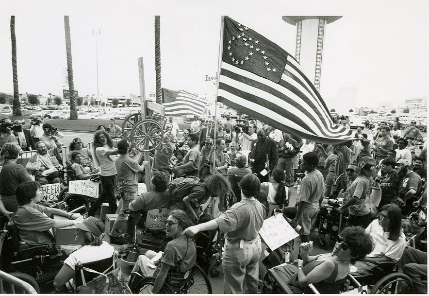 A large crowd at a rally, many of the people use wheelchairs. they hold a U.S. Flag with the stars in formation of a wheelchgair disability symbol.