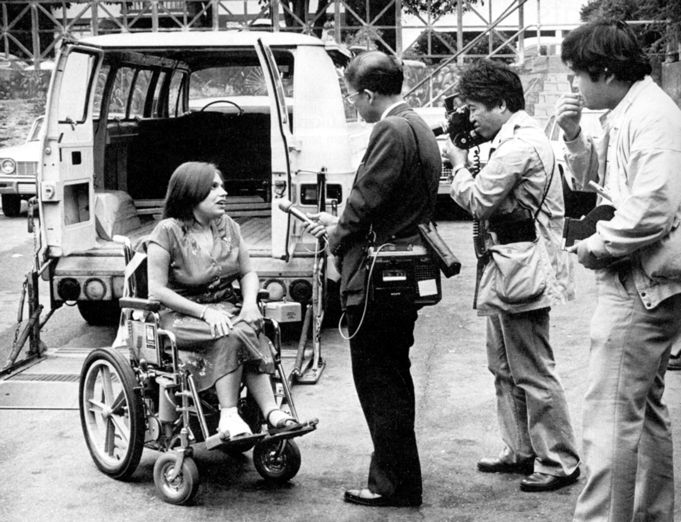 Disability rights icon Judy Heumann sits in her wheelchair being interviewed by members of the television press in fron of a van at the 504 Protest.