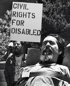 "A picture of Ed Roberts in his wheelchair, behind himn a man stands and holds a sign that says: ""CIVIL RIGHTS FOR DISABLED."""