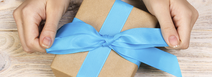 hands tying a ribbon on a gift box