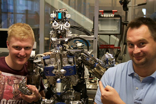 UQ QURPA-funded student Josh Riddell and UQ PhD student Nikodem Rybak with a UCSD robot.