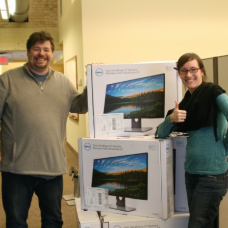 Staff pose with new computer monitors