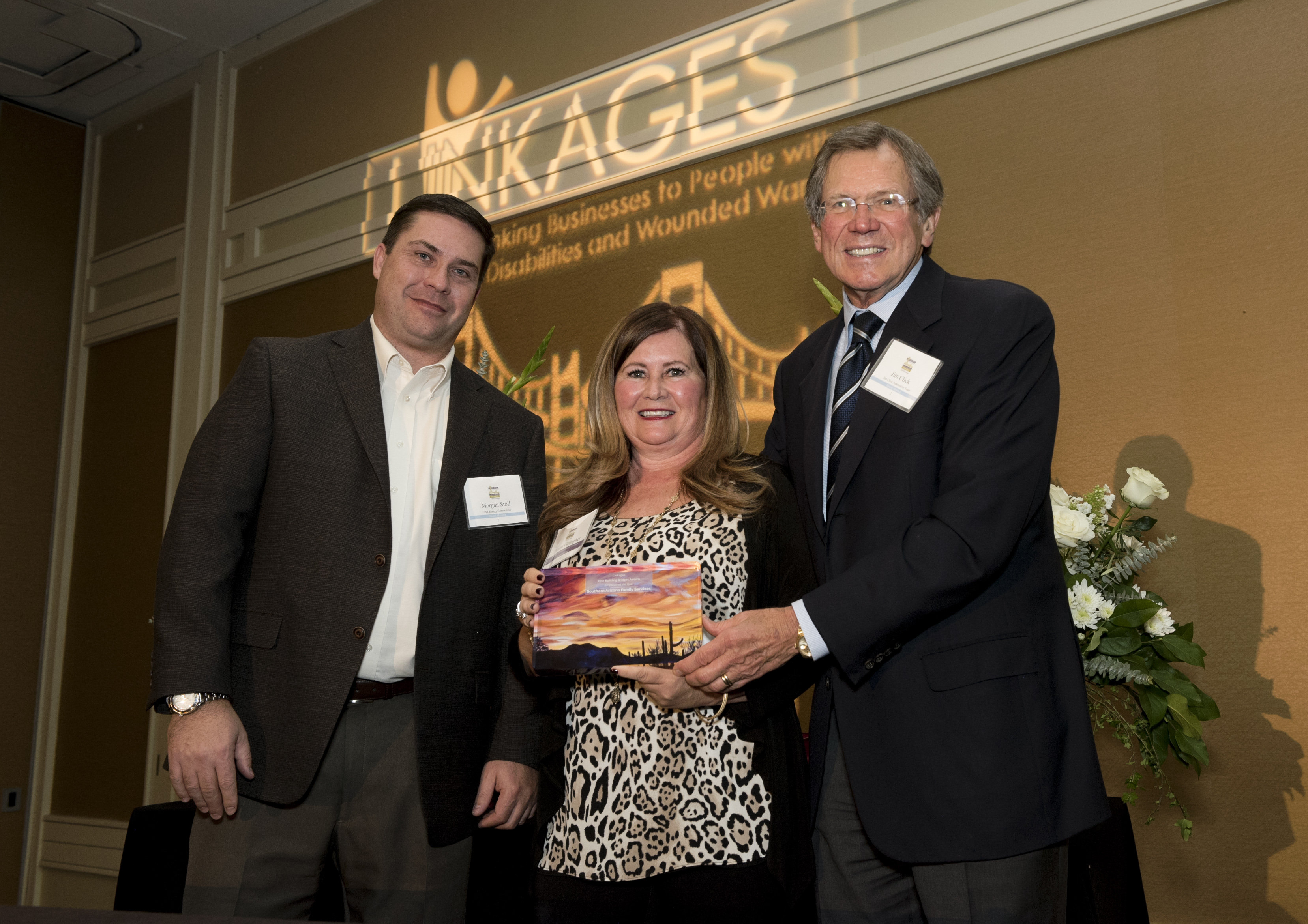 Morgan Stoll and Jim Click giving Donna Gallagher the employer of the year award. Donna is in the middle of them holding her award.