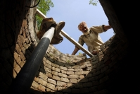 A farmer looking down his well