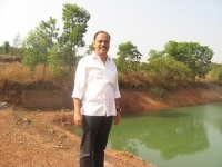 Rajesh Naik near the lake he has developed at the Oddoor farms near Mangalore