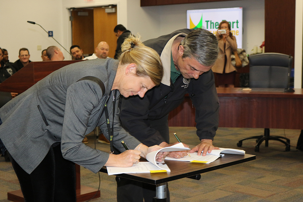 Kristin Decas, CEO and Port Director, and Tony Skinner, President of the IBEW Local 952, sign the historic agreement