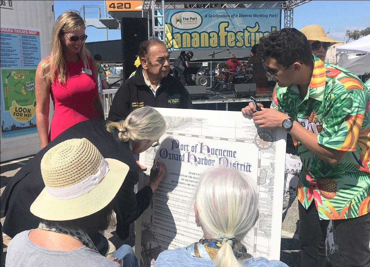 Supervisor Kelly Long and OHD President Jess Herrera look on as Port Founder Richard Bard's daughter Joanna Bard Newton and grandson Henry Travers Newton sign the Port's Clean Air Day Resolution