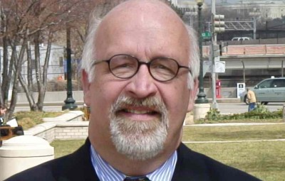 Headshot of Claude Stout. White man, bald with white hair and salt/pepper goatee with round-rimmed glasses.