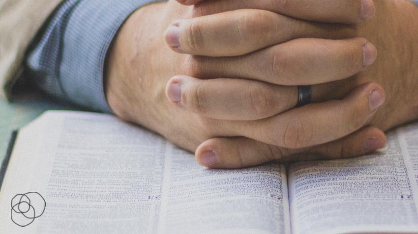 praying hands on Bible