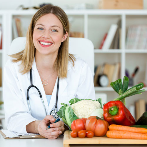Smiling dietitian with vegetables.