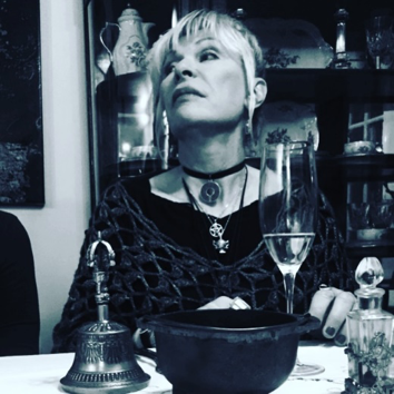Patti Negri sitting a table, performing her magic.