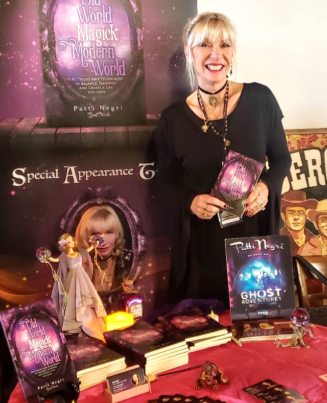Patti Negri holding a copy of her book, OLD WORLD MAGICK FOR THE MODERN WORLD.