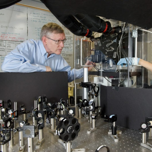 Professor W. E. Moerner, left, and postdoctoral scholar Anna-Karin Gustavsson position a sample on the new TILT3D microscope.