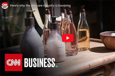 video still from CNN Business showing beauty product bottles on a table