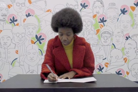 screenshot from New York Daily News video with Ebony Bolt sitting at a table with her sketches on a wall behind her