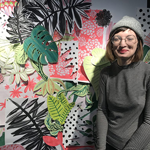 Bethany Robertson standing in front of her collage of illustrated leaves