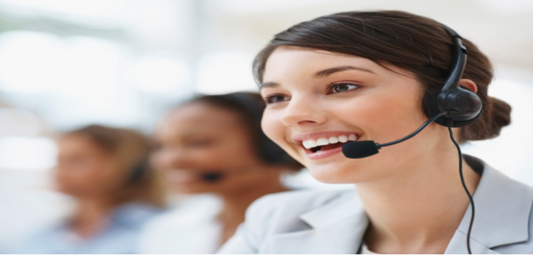 Customer service employee wearing a set of headphones and smiling