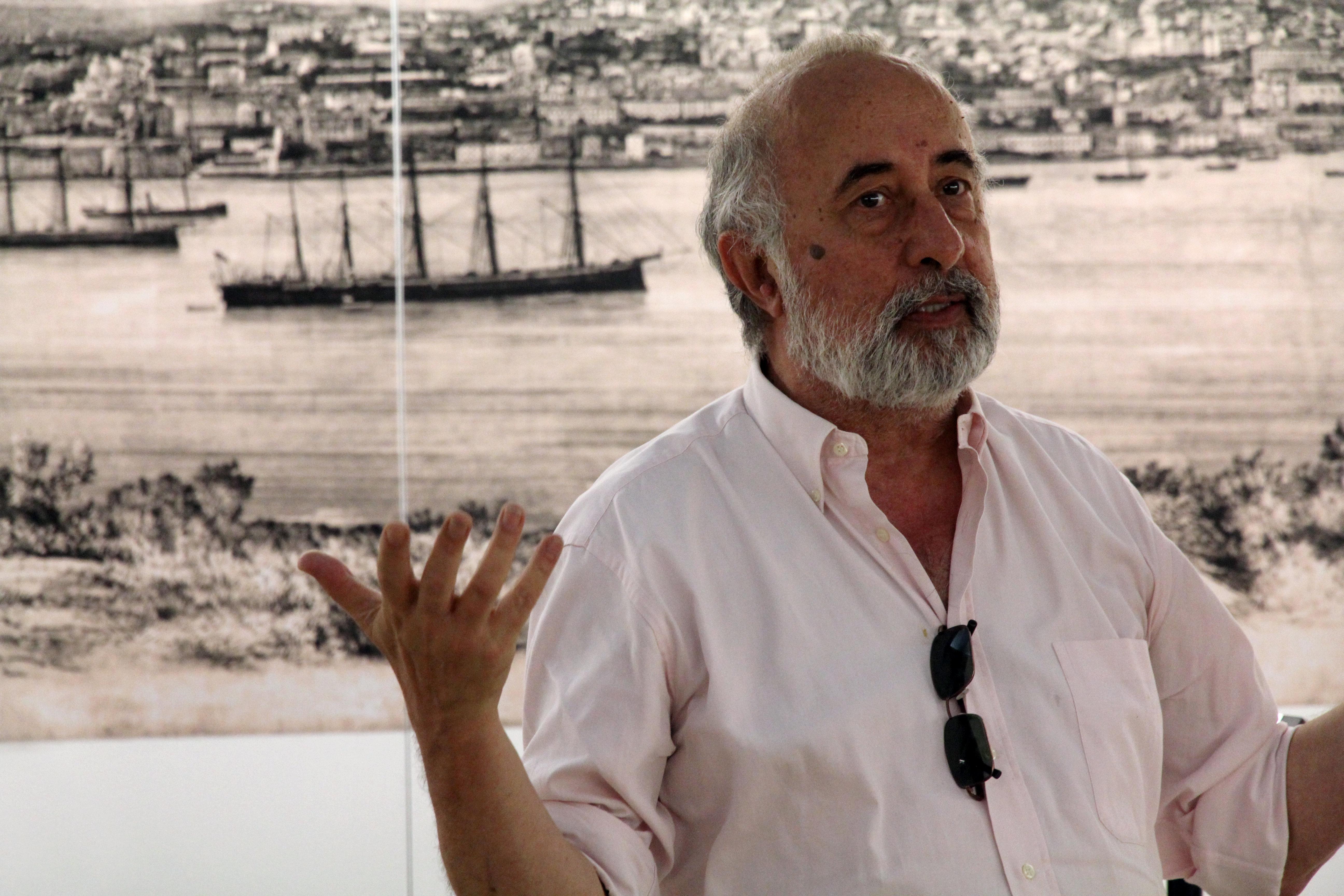 José Sarmento Matos com um ar sério, e com os braços ligeiramente erguidos como quem explica algo, com uma imagem de Lisboa atrás (a preto-e-branco, existem barcos, um rio e a cidade por trás)
