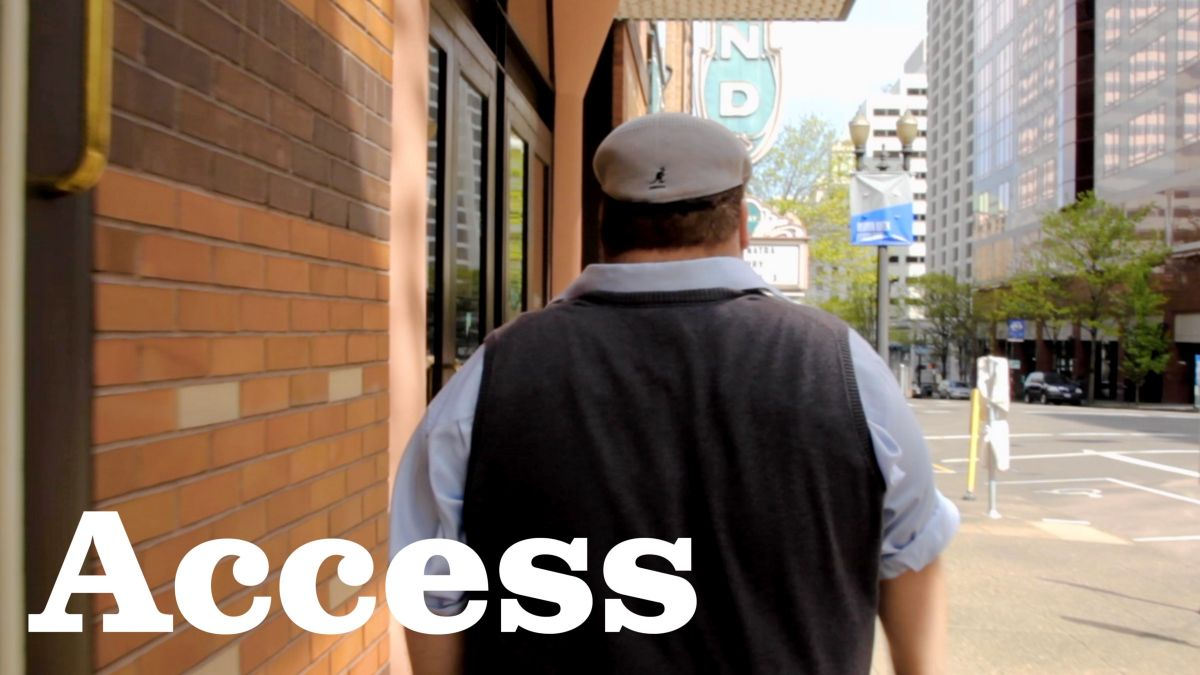 "Man walking down sidewalk, text ""Access"""