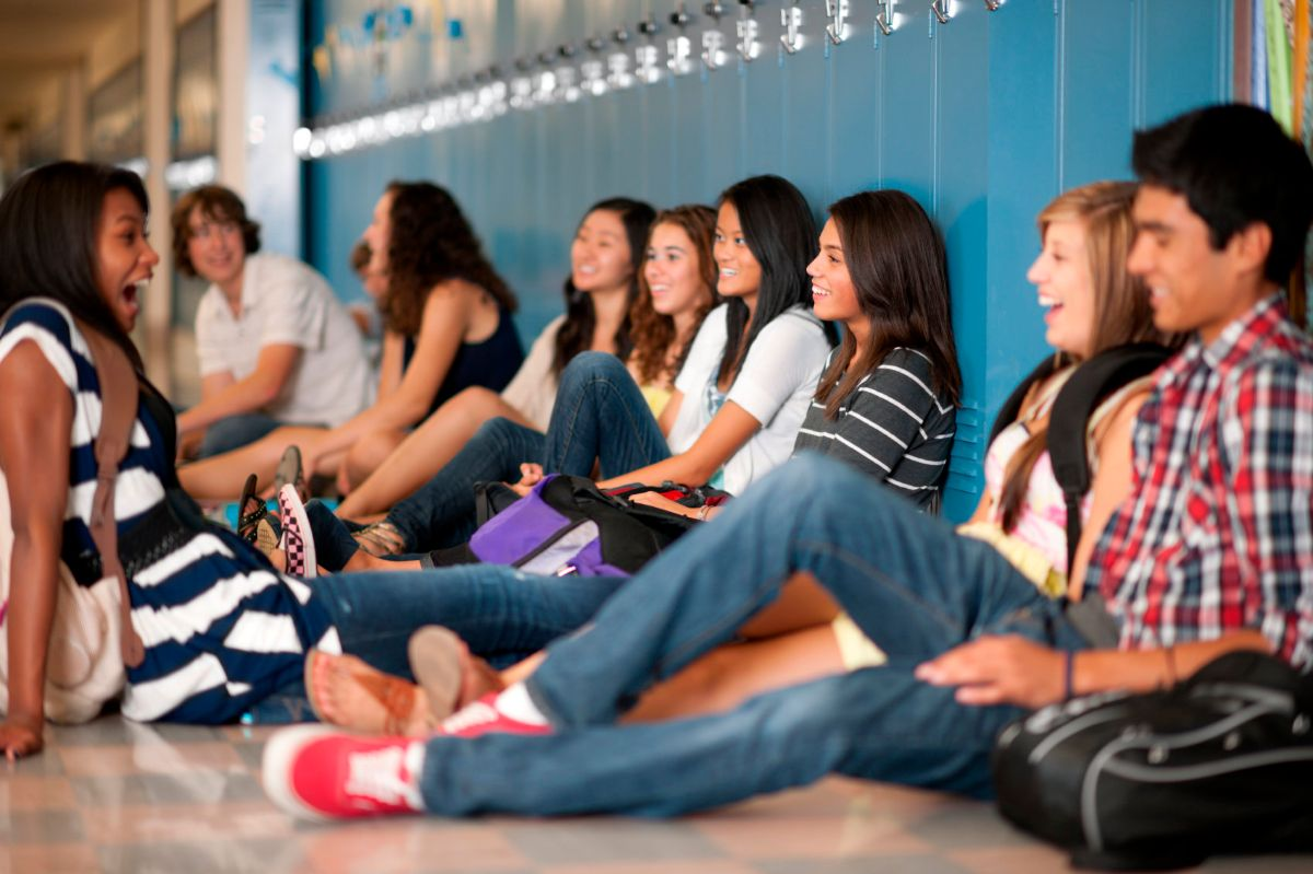 Diverse group of students sitting in high school hallway