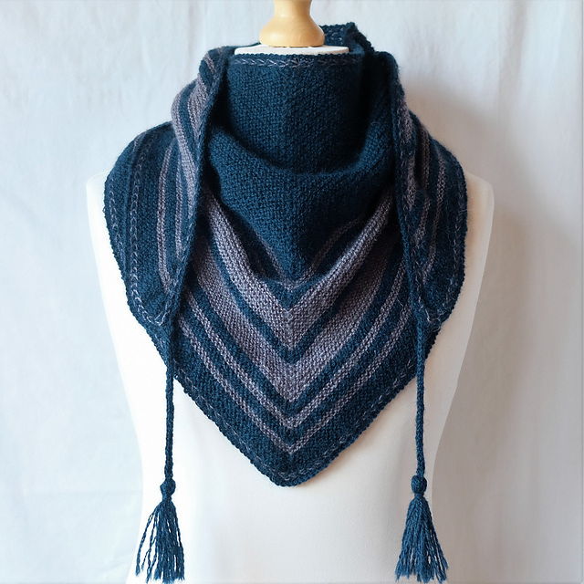 A triangular shawl with tassels wrapped around a mannequin, in teal blue with grey stripes