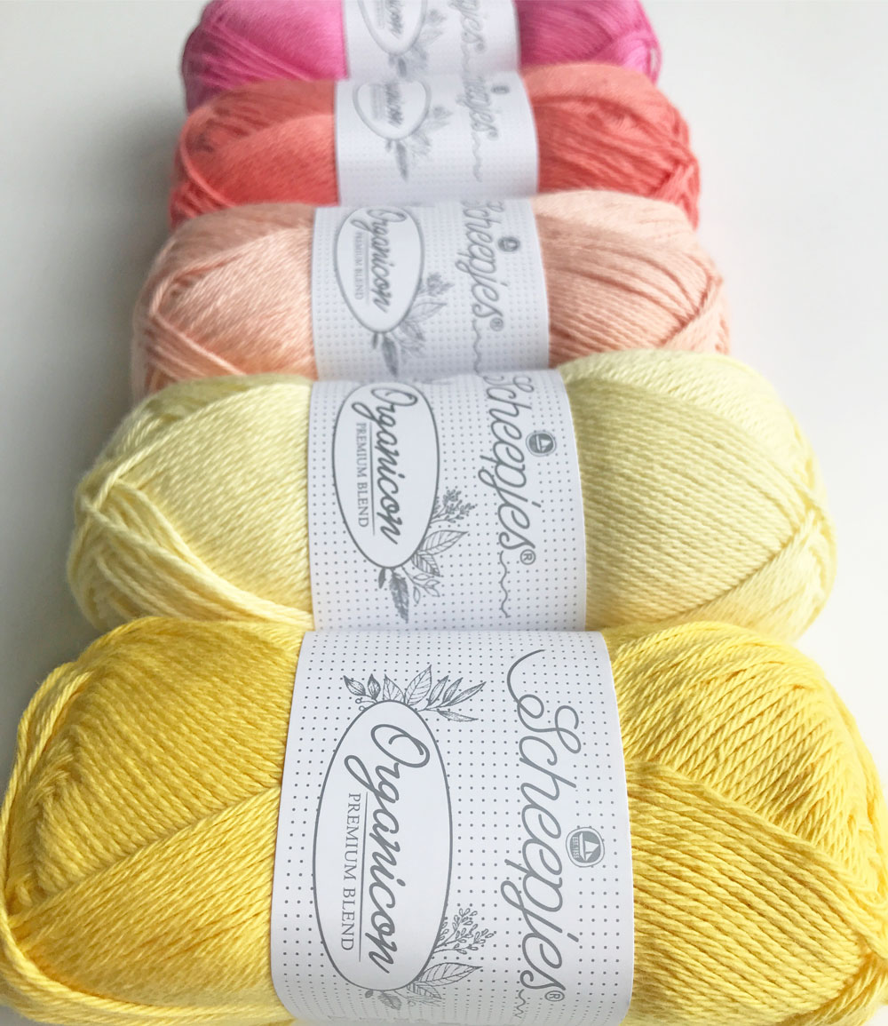 A queue of Scheepjes cotton yarn, from Gentle Primrose at the front to Apple Blossom at the back
