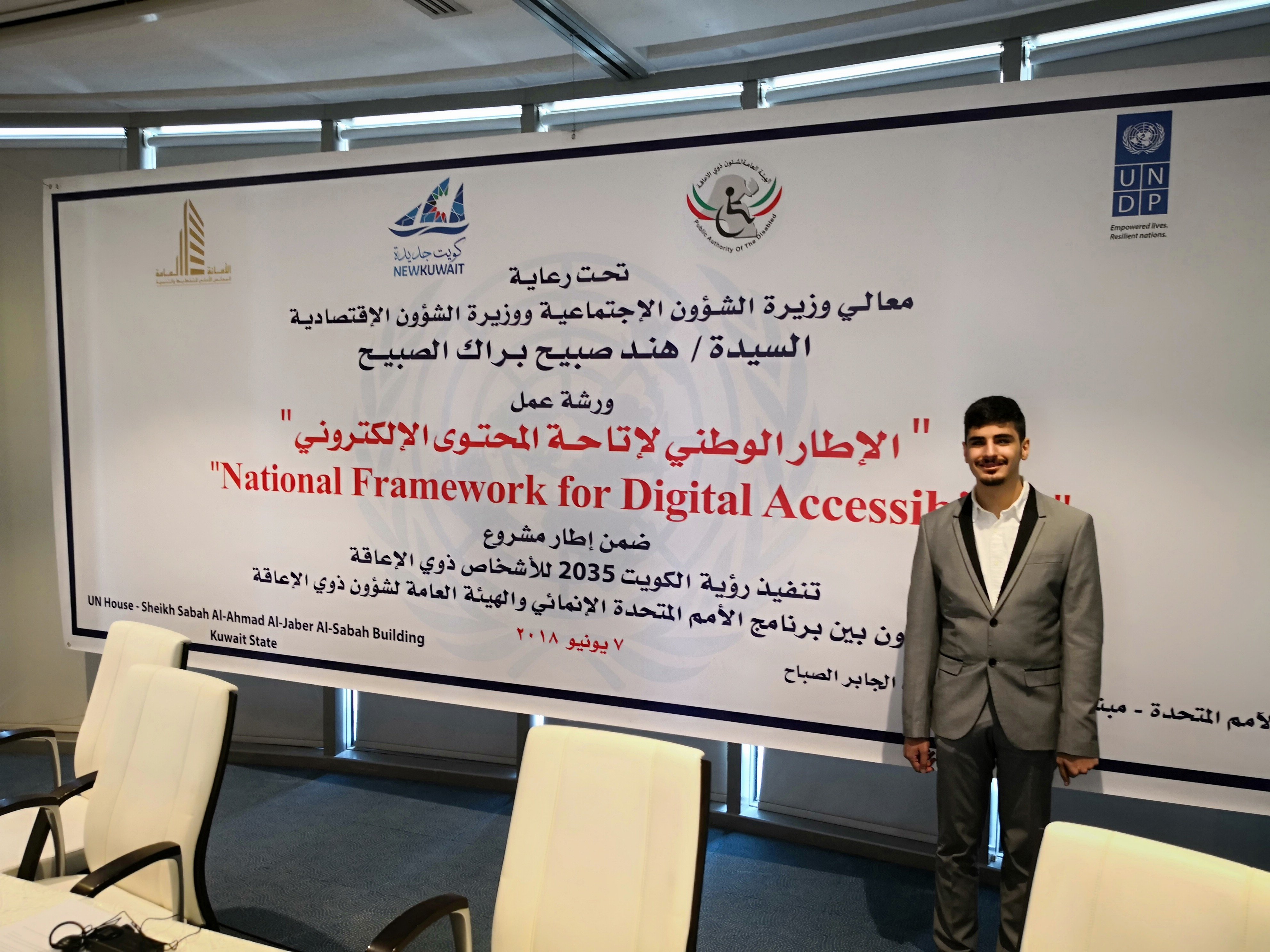"""Photo of Ahmad Albahar in front of a banner in arabic that says """"National Framework for Digital Accessibility"""""""