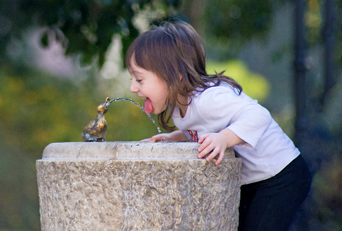 Drinking water fountain with girl