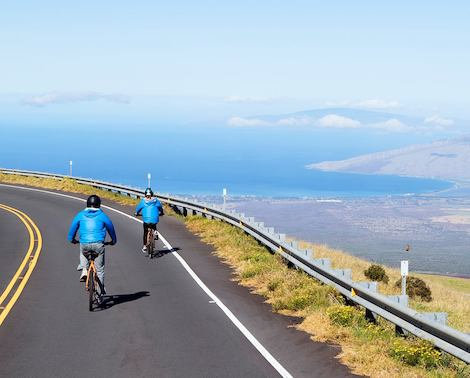 Two bicyclists riding downhill on Haleakala with view of the ocean, island of Maui