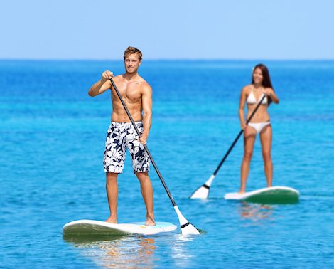 A young couple on SUP boards in the middle of a blue ocean