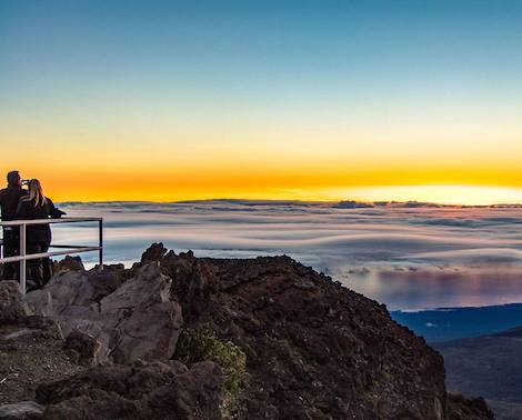Two people observing sunrise at Haleakala Crater on the island of Maui