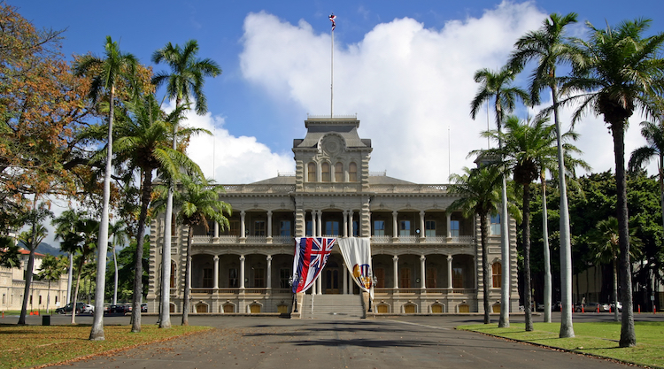Front view of Iolani Palace at the end of coconut tree-lined entrance in Honolulu, Hawaii