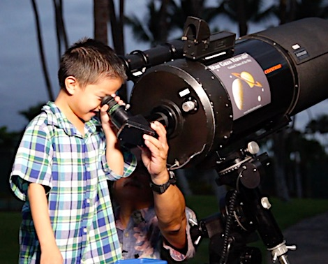 Young boy looking through the base of a telescope on the Big Island of Hawaii