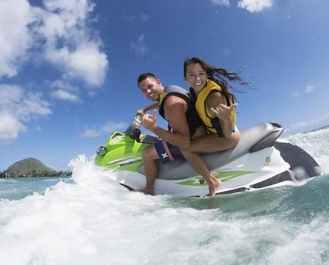 Man and woman riding the waves on a jet ski off the eastern coast of Oahu
