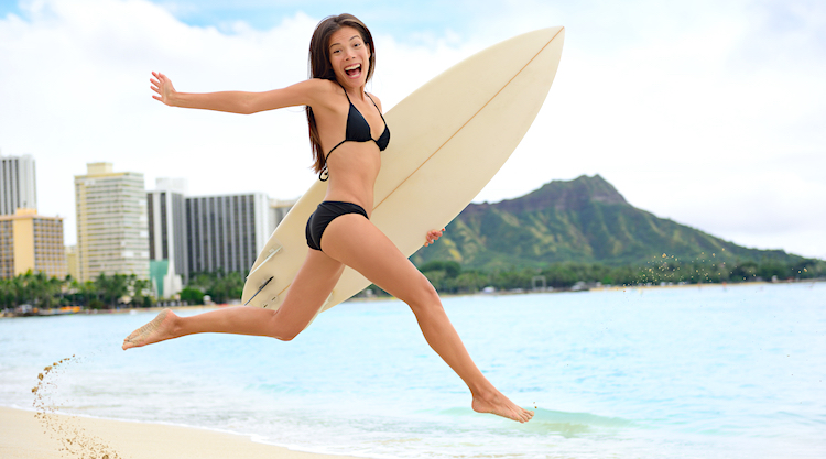Young woman holding surfboard and leaping at Waikiki Beach with Diamond Head in background