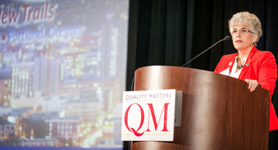 Deb Adair standing at a podium with a QM sign on it