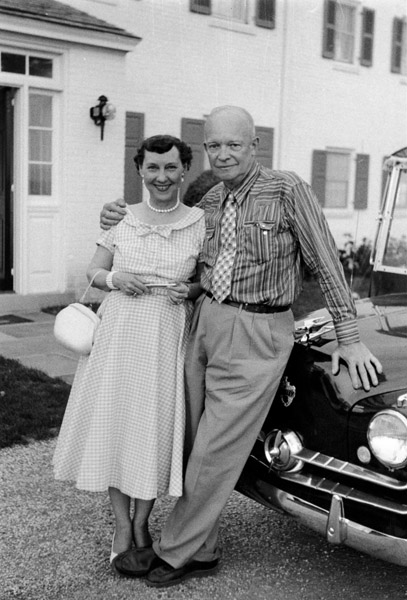 Dwight and Mamie Eisenhower lean against a car