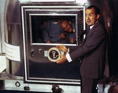 Photograph of President Nixon greeting the Apollo 11 astronauts during quarantine