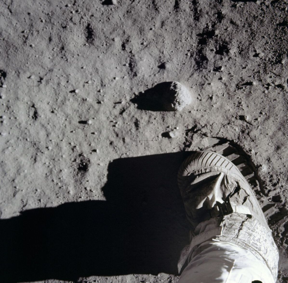 Photograph of lunar surface with astronaut boot in field of view