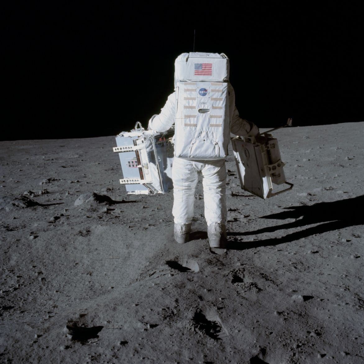 Photograph of Astronaut Edwin Aldrin carrying equipment on the moon