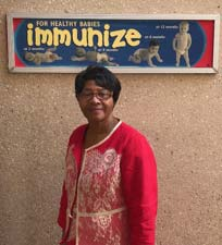 Texas NAACP Health Committee Director Carol Moore stands under a sign advertising 'For healthy babies, immunize'