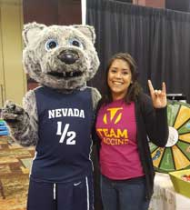 Mascot in a wolf costume wearing a basketball jersey with Nevada 1/2 printed on it has his arm around a young woman wearing a shirt that says Team Vaccine
