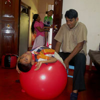 A child using a balance ball in a therapy session