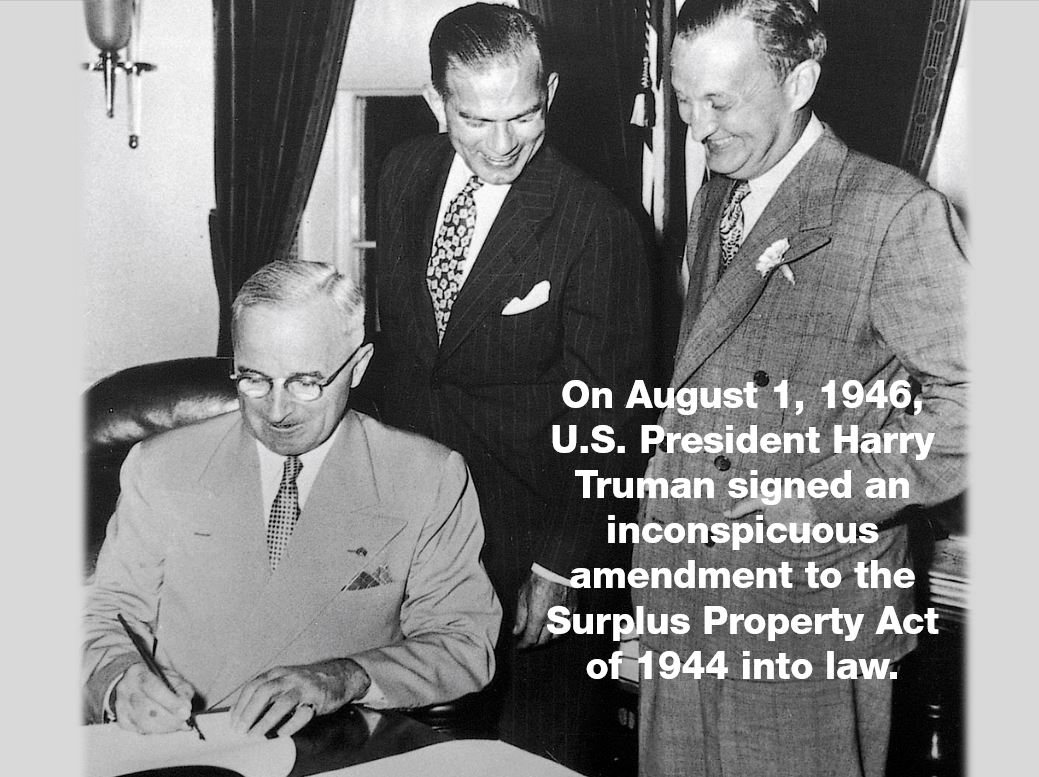 President Harry Truman signing the Fulbright Act with Senator Fulbright behind him.