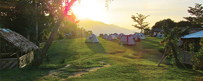 Sun setting on peaceful, green camping grounds dotted with tents