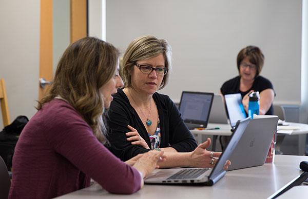 Professor Beth Herbel-Eisenmann discusses practices with a teacher.