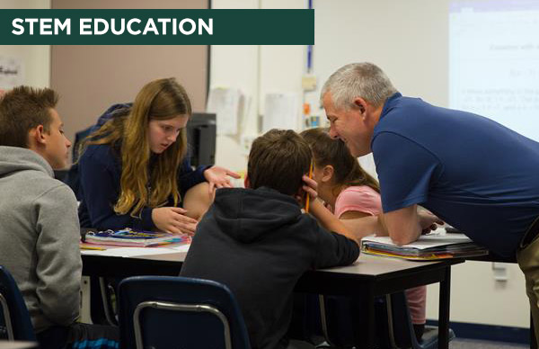 MSU alumnus works with students in math class.