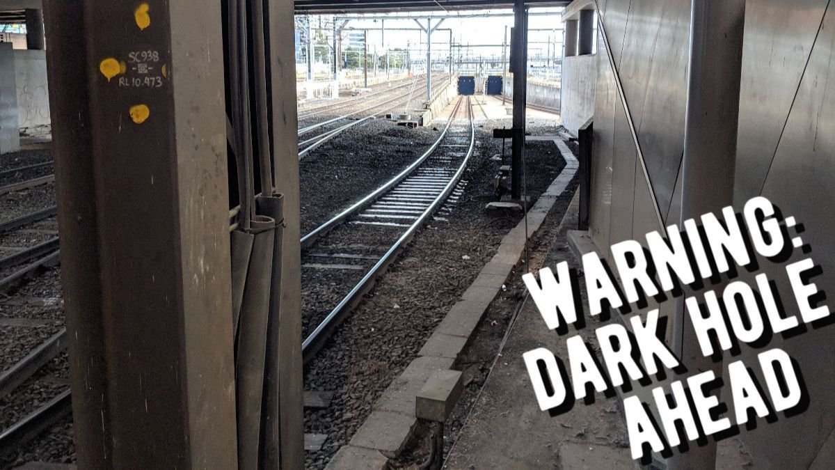 Train tracks leading into dark tunnels. Text: Warning, Dark Hole Ahead