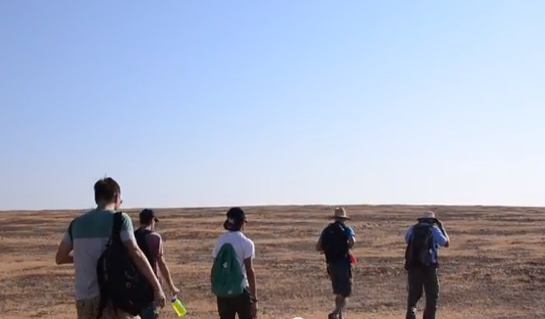 People hike over short brown grass into the Merced Vernal Pools and Grassland Reserve